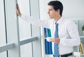 Young businessman looking through the office window while drinking coffee